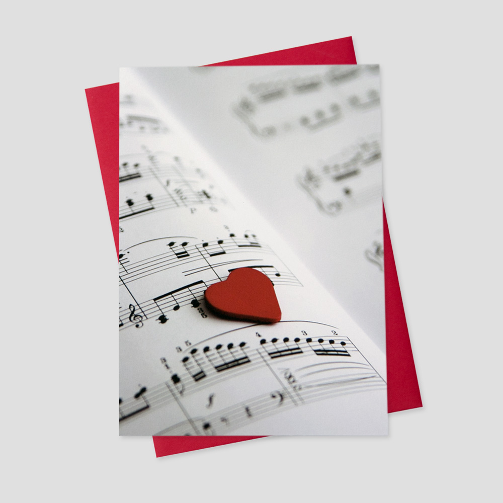 Company Valentine's Day greeting card featuring a music sheet with musical notes and a red heart perched on the page