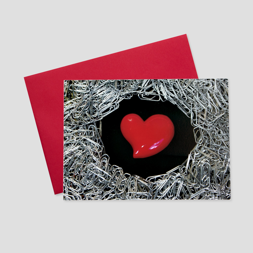 Employee Valentine's Day greeting card featuring a red heart on a black background surrounded by paper clips