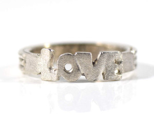 The sterling silver love ring is hand crafted in Portland, Maine.  The love ring is a size 6 and weighs 3.2 grams. The ring is 5 mm. wide with a multirow band.