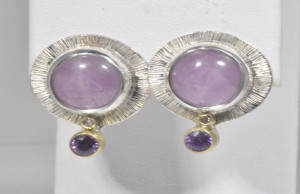 The earrings are kunzite and purple sapphire, that are hand crafted in Portland, Maine.  The kunzite is a 12 mm. round cabochon.  There is  a 1.8 mm. round brilliant cut diamond and a 44.3 mm. round purple sapphire on each earring.  The earrings are sterling silver and 18 k yellow gold with a slash effect around the kunzite.  The earrings weigh 8.8 grams and measure 24 mm. x 20 mm. x 6 mm.