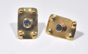 The gold blue topaz earrings are hand crafted in Portland, Maine.  The center stone is a 4 mm. round Swiss blue color and is bezel set.  The stone is set in 14 K yellow gold a with a polished finish.  The earrings weigh .2 grams and measure 20 mm. x 11 mm.  The blue topaz is the December birthstone.