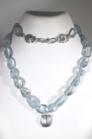 The aquamarine strand is hand crafted in Portland, Maine.  The strand consists of aquamarine free form beads measuring 10 mm. wide but varying in length and weighs 38.7 grams.  The strand is 18.5 inches in length.  There is a sterling silver three dimensional shell on the front measuring 14 mm. x 12 mm.  The clasp is also a double shell with a fish hook and the shells measure 11 mm. x 9 mm.  The aquamarine is the birthstone for March.  March Birthstone
