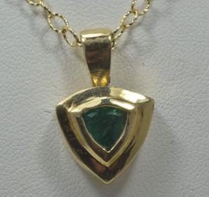 The emerald faceted trillion pendant is handcrafted in Portland Maine.  The emerald is .89 carats and measures  6.2 mm. The pendant is set in a 18 k yellow gold bezel and frame that is solid.  The pendant weighs 8.4 grams.  The emerald has a bright green color and the pendant measures 15 mm.  The chain is sold separately.