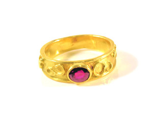The swirl gold ruby ring is hand crafted in Portland, Maine. The ring is cast in 18 k yellow gold and has shapes of swirl patterns on the band. The ruby is a Fine ruby, roval in shape and measures 5 mm. x 4 mm. The ring weighs 4.5 grams and measures 5.5 mm. tapering to 4 mm. The ring can be sized, upon request.