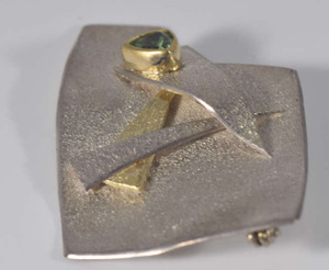 The textured silver and gold tourmaline pin is hand crafted in Portland, Maine. The pin has a textured finish and is sterling silver and 18 k yellow gold. The pin has a 6 mm. mint color green Maine tourmaline. The pin measures 1.5 x 1.25 inches and weighs 10.2 grams.
