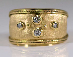 The gold four diamond ring is hand crafted in Portland, Maine. There are four round diamonds having a carat weight of .16 carats. The diamonds are G in color and SI 2 in clarity. The stones are set in an 18 k yellow gold Etruscan style mounting. It is 12 mm. wide at the top. The ring can be sized upon request.