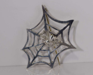 The sterling silver spider web pin is a hand crafted one of a kind pin. The pin measures 2 x 1.75 x .5 inches and weighs 7.1 grams. The pin has a spider on it measuring .75 x.5 inches.