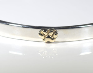 The silver and gold paw bangle is hand crafted in Portland, Maine. The bangle fits a 7 inch wrist size and is 5.5 mm. wide and is sterling silver. There are four 18 k yellow gold paws on it, measuring 7 mm. x 5 mm. The thickness of the bangle is 1 mm. and with the paws it is 3.5 mm. The bangle has a polished finish and weighs 20 grams. A portion of the profit will be donated to The Animal Refuge League, in Westbrook, Maine.