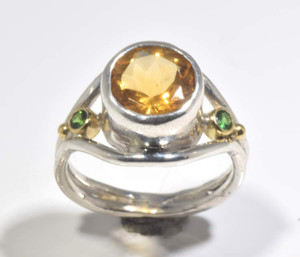 The citrine and tsavorite ring is hand crafted in Portland, Maine.  the citrine is a 9 mm. round and there are two 2.5 mm. round tsavorite garnets.  The garnets are set in 18 K yellow gold bezels and the ring is sterling silver. The ring is a size 6.5 and weighs 5.0 grams.  The center of the ring measures 14 mm. and tapers to 3 mm.  The style is a split shank.