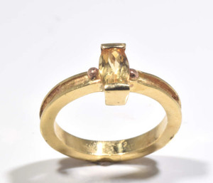 The Imperial topaz gold ring is hand crafted inn Portland, Maine.  The topaz is a 8 mm. x 4.5 mm. antique cushion cut.  The stone is set in a 14 k yellow gold bar setting with two beads one on either side of a 2.5 mm. concave band.  The ring is a size 6 and weighs 3.9 grams.
