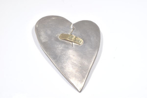 The broken heart pin is hand crafted in Portland, Maine.  The pin is sterling silver and has an 18 K yellow gold band aid across the crack.  The pin measures 2 x 1.25 x .25 inches and weighs 8.7 grams.  the pin is a one of a kind