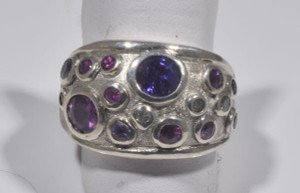 The sterling silver multi sapphire ring is hand crafted in Portland, Maine.  The ring is a multi bezel style in sterling silver weighing 9.6 grams.  There is a 5.5 mm. purple, 5 mm. pink and three 3 mm. pink and purple set with eight  1.8 - 2.25 mm pink and purples.  there are four 1.8 mm. round brilliant cut diamonds.  the diamonds have an approximate total weight of .14 carats with a color of J and a clarity of I1.  There is 17 stones in total.  All stones are bezel set in a random pattern.  The ring is a size 7 and the top measures 15 mm. and taperers to 2.75 mm. with the top domed.