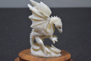 caved fossilized Ivory dragon stationed on a oak stand, with sapphire eyes