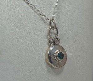 The sterling silver round emerald pendant is a simple handcrafted solitaire.  The emerald is a clean bright medium light green color. The stone weighs .27 carats and measures  4 mm. The pendant is a polished sterling silver beaded bezel drop style pendant weighing 2.8 grams and measures 14 mm. in diameter with a length of 38 mm.  The chain is sold separately.  The emerald is the birthstone for May.  To ensure that your package arrives to you safely, there will be a 2% handling fee for additional insurance on international shipping.