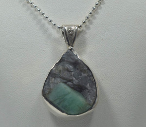 The rough emerald pear shaped pendant is handcrafted in Portland, Maine.  The pendant is a sterling silver bezel set heavy pendant style.  The emerald is in its rough form.  The pendant is sold with out a chain.