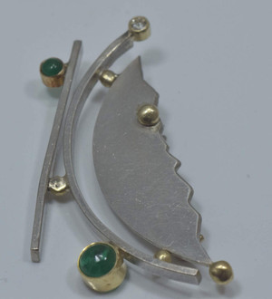 This contemporary emerald and diamond pin was handcrafted in Portland, Maine  The pin is sterling silver, 22k, and  18k yellow gold.  The pin has a geometric shape with two emerald cabochons one 5 mm. and one 3 mm. the emeralds are an opaque bright green color.  There is a 2 mm. round brilliant cut diamond.
