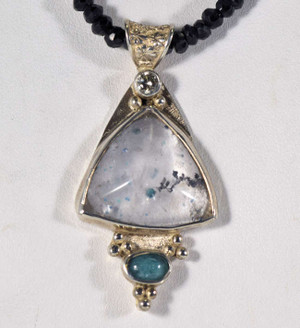 """The Paraiba tourmaline in quartz necklace is handcrafted in Portland, Maine. The piece is a real one of a kind. The triangle shaped quartz measures 22mm.x19mm.x18.5mm and also has black tourmaline in it. There is also an oval Paraiba cabochon on the bottom measuring 7mm.x5mm. At the top of the stone there is a round brilliant cut diamond that is .2carats. The color of the diamond is """"j"""" and clarity is """"I1"""". The stones are set in sterling silver and the pendant measures 2x1 inches and weighs 20.6grams. This is on a 4mm. faceted rondelle, black garnet strand. The necklace is 17.5 inches and length."""