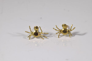 The gold spider stud earrings are hand crafted in Portland, Maine.  The spiders are 18 K yellow gold with 14 K yellow gold posts and ear nuts.  the spiders measure .75 x .5 x .6 inches and weigh 1.4 grams.