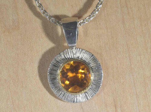 The two tone citrine pendant is hand crafted in Portland, Maine.  The citrine is a 9 mm. round faceted stone, with a checkerboard table.  The stone is set in a 18 K yellow gold bezel and a round sterling silver slash style frame.  The pendant weighs 3.3 grams and measures 16 mm. x 23 mm. x 6 mm.  The bail will fit a 3 mm. chain.