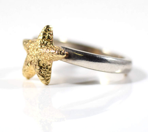 The two tone starfish ring is hand crafted in Portland, Maine.  The ring has a 3 mm.  x 2 mm. sterling silver shank and is size 6.  There is a 14 k yellow gold textured starfish measuring 11 mm. x 3 mm. and the ring weighs 4.9 grams.
