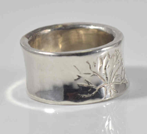The sterling silver tree of life ring is hand crafted in Portland, Maine. The ring is is 10.3 grams and measures 11 mm. x 2 mm. and is a size 7 slight.  The ring can be sized upon request.