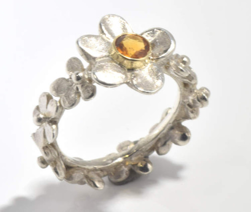 The citrine sterling silver flower ring is hand crafted in Portland, Maine.  The ring has a 4.25 mm. round citrine set in a sterling silver flower measuring 14 mm. x 13 mm. and a flower band measuring 7.5 mm. wide.  The ring weighs 5.6 grams.  The flowers go all around the band.