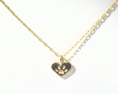 The tiny gold pet paw heart pendant is hand crafted in Portland, Maine.  The pendant is a 14 k yellow gold heart that measures 6.2 mm. x 8.2 mm. x 1 mm. and weighs .5 grams.  A portion of the profits is donated to the animal Refuge League of greater Portland, Maine.