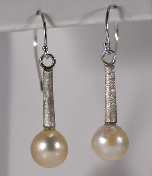 The baroque pearl drop earrings are hand crafted in Portland, Maine.  The pearls are a white 9 mm. baroque salt water pearl. The drops are a textured sterling silver with a hook drop.  The earrings are 1.75 x .4 x .4 inches and weigh 4.3 grams.