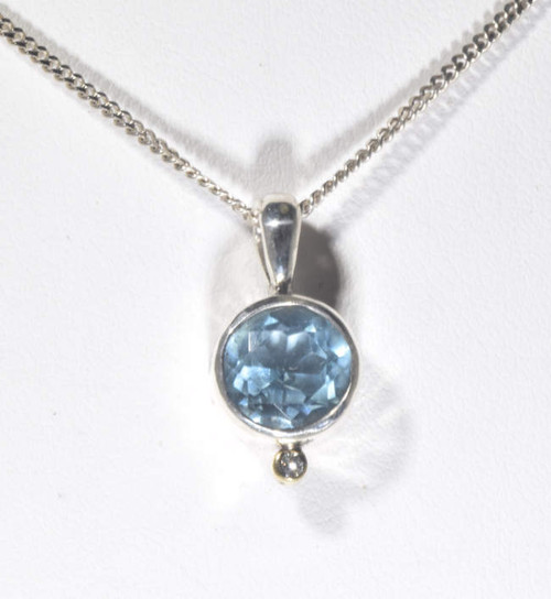 The sky blue topaz pendant is hand crafted in Portland, Maine.  The blue topaz is a round 9 mm. sky blue color.  The stone is set in a sterling silver bezel with a 18 K gold bezel with a 1.8 mm. round brilliant cut diamond.  The pendant weighs 3.1 grams and measures 3/4 x 3/8 x 1/4 inches.  The chain is sold separately.  Blue topaz is the December birthstone.