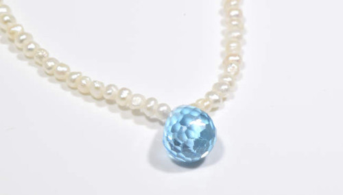 The blue topaz briolette drop pendant is hand crafted in Portland, Maine.  the briolette is a 9 mm.x 7.5 mm. and it is on a 2- 2.5 mm. fresh water baroque pearl strand.  The strand has a sterling silver fish hook clasp and measure 17 inches in length.  Blue topaz is the December birthstone.