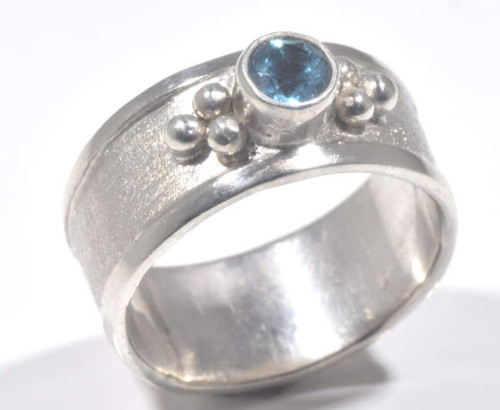 The blue topaz silver ring is hand crafted in Portland, Maine.  The blue topaz is a 4.5 mm. round Swiss blue set in a sterling silver brushed and beaded band.  The ring is a 7 mm. wide band and a size 7.5.  The ring weighs 7.0 grams.  Blue topaz is the December birthstone.