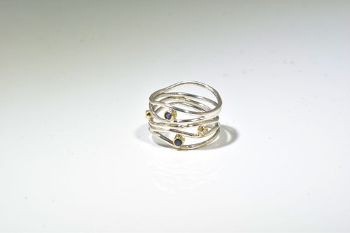 The blue sapphire and diamond wire ring is handcrafted in Portland, Maine.  The ring has two 2.25 mm. round fine blue sapphire and two 1.8 mm. round brilliant cut diamonds. The stones are set in 18 K yellow gold bezels and the ring itself is sterling silver.  the ring weighs 4.5 grams and it widest pint is 15 mm.  The wire ring is has a polished finish and is a size 7.5.  Sapphire is the September birthstone.