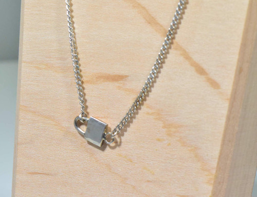 The sterling silver padlock necklace is hand crafted in Portland, Maine.  The necklace is 16 inches in length and weighs 3.2 grams.  The chain is a 1.5 mm. curb style.  The lock is solid and  is sterling silver.  The lock measures .5 inches x .3 inches.