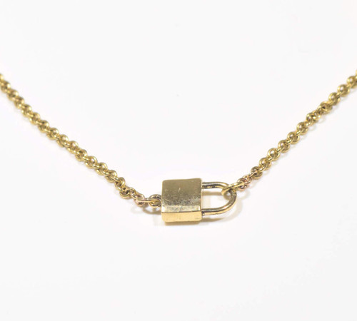 The gold Padlock necklace is hand crafted in Portland, Maine.  The necklace is 14 K yellow gold and is solid. The lock is .5 inches x .3 inches and is 16.5 inches in length.  The necklace has a link style chain that is 1.3 mm. and weighs 3.6 grams.