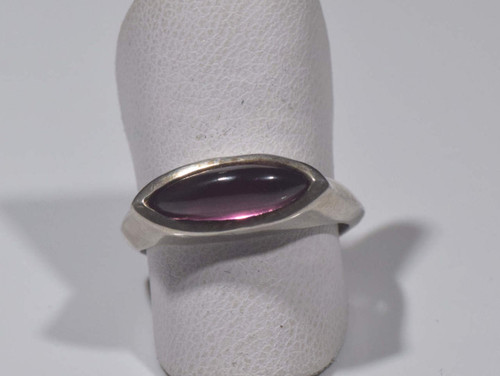 The marquis garnet sterling silver ring is handcrafted in Portland, Maine.  The garnet is a 4.5 mm. x 3 mm. x 3 mm. marquis cabochon rhodolite garnet.  the stone is set horizontally in a bezel in a contemporary silver ring that is a size 6.5.  To ensure that your package arrives to you safely, there will be a 2% handling fee for additional insurance on international shipping.