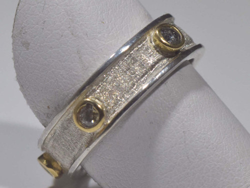 The mixed metal five diamond ring is handcrafted in Portland, Maine.  The ring is a size 6.75 band that is sterling silver with 18 K yellow gold bezels.  There are five diamonds that have a total carat weight of .20, a color of J and a clarity of I1.  The band is 5.5 mm. wide and 2 mm. thick at the widest point.  the band has a brushed and polished finish and weighs 5.4 grams.