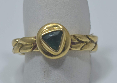 The 18k yellow gold braid band emerald ring is handcrafted in Portland, Maine.  The emerald is a 5 mm. faceted trillion shape.  The emerald is darker green with good saturation.  The ring is a size 8.5 and weighs 10 grams.  The shank is 4.2 mm. wide.