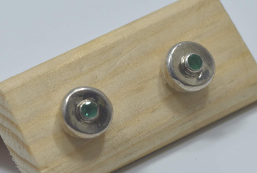 There are 2 mm. round medium green emeralds set in a sterling silver stud.  The earrings are handcrafted in Portland, Maine.  The setting measures 7 mm. and 2.75 mm. deep, with a gram weight of 2.8 grams.  The earrings have a polished finish.  Emeralds are the birthstone for May.