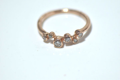 The  rose gold diamond pebble band is handcrafted in Portland, Maine.  The ring has six round brilliant cut diamonds set in individual bezels.  The diamonds have a total weight of .38 carats and range from 1.8 mm. to 3.2mm.  The color of the diamonds is J and the clarity is I1.  The stones are set in 14K rose gold size 7.75.  The ring weighs 2.8 grams and the shank is around 1.8 mm. o ensure that your package arrives to you safely, there will be a 2% handling fee for additional insurance on international shipping.