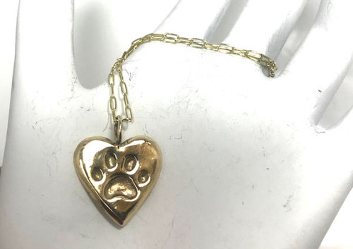 "The gold paw print heart pendant is handcrafted in Portland, Maine.  The pendant is 14K yellow gold and weighs 3.5 grams.  The pendant measures 5/8"" x  5/8"" and is 1.5 mm. thick.  The pendant is on a 14k yellow gold elongated oval link chain.  The chain is 20 inches in length and measures 1. 3 mm. wide with a lobster claw clasp.  The chain weighs  2.1 grams.  If you would like a different chain or chain length please contact us."