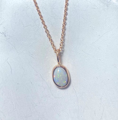 The opal pendant is hand crafted in Portland, Maine.  The opal is a 7mm. x 5 mm. and is set in a 14k rose gold bezel that is solid on the back.  The pendant  weighs 2.6 grams with the chain. the opal pendant is on a 1.3 mm. curb chain that is 18 inches in length.  Opal is the birthstone for October To ensure that your package arrives to you safely, there will be a 2% handling fee for additional insurance on international shipping.