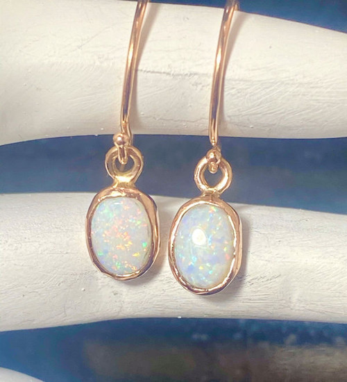 The rose gold opal earrings are hand crafted in Portland, Maine.  the opal is a 7 mm. x 5 mm. oval set in a 14k rose gold bezel.  The back is solid and dangles from the hook.  the earrings weigh 1.6 grams and are 15/16 of an inch in length.  Opal is the birthstone for October.
