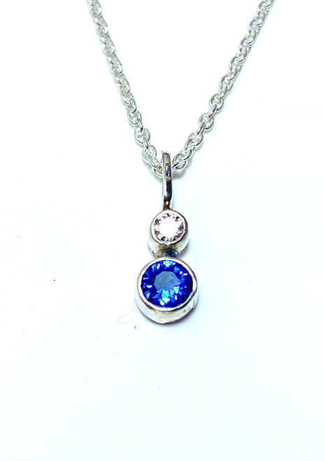 The sapphire and diamond silver pendant is handcrafted in Portland, Maine.  The sapphire is a 3.5 mm. round AAA blue Ceylon, with a 2.5 mm round brilliant cut diamond.  The diamond is a G in color and SI1 in clarity.  The stones are bezel set in sterling silver weighing 2.0 grams.  The pendant is on a 18 inch 1 mm. sterling silver curb style chain.  September birthstone is sapphire.