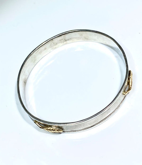 The bangle is handcrafted in Portland, Maine.  The bangle is a 10 mm wide solid slide on.  The bangle is sterling silver with a polished edge.  There are four 14 K yellow gold carved leaves positioned (NSEW) on the bangle.  The bangle weighs 29.3 grams.
