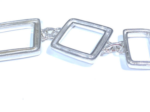 The Open square link bracelet is handcrafted in Portland, Maine.  The bracelet has square and rectangle sections, that are open with a grooved section each link.  the bracelet is 1 inch wide at its widest and weighs 26.1 grams.  This bracelet i very contemporary and is solid.  The length of the bracelet is 7.5 inches.