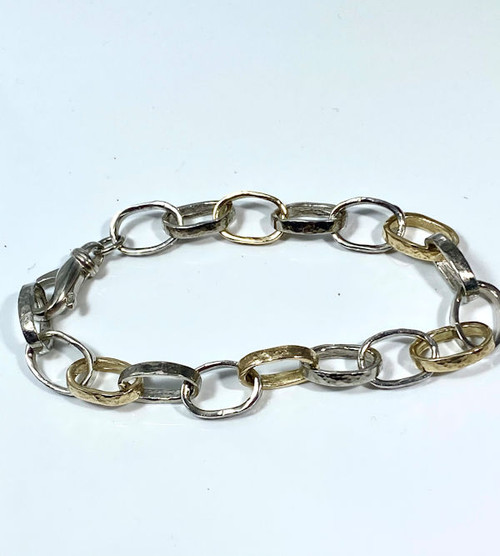 The two tone hammered link bracelet is handcrafted in Portland, Maine.  The bracelet has sterling silver oval hammered links and 14 K yellow gold links.  The links measure 11 mm. x 9 mm. and the bracelet weighs 12.2 grams.  There is a lobster claw clasp and the bracelet is solid.