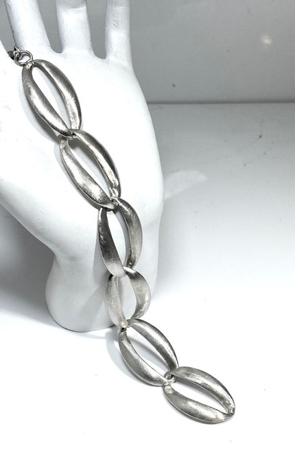 The brushed oval link bracelet is handcrafted in Portland, Maine.  The bracelet is sterling silver and has large oval brushed links measuring 25 mm. x 15 mm.  the bracelet has 6 links and is 7 inches in length.  This bracelet weighs 12.2 grams and is solid.