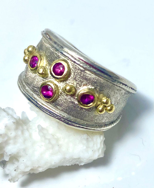The pomegranate sapphire ring is handcrafted in Portland, Maine.  There are four round faceted pomegranate sapphires 2.5 mm. and are set in sterling silver and 18 K yellow gold.  The ring weighs 9.6 grams and measures 13.5 mm wide and tapers to 5.5 mm.  The ring is a size 6