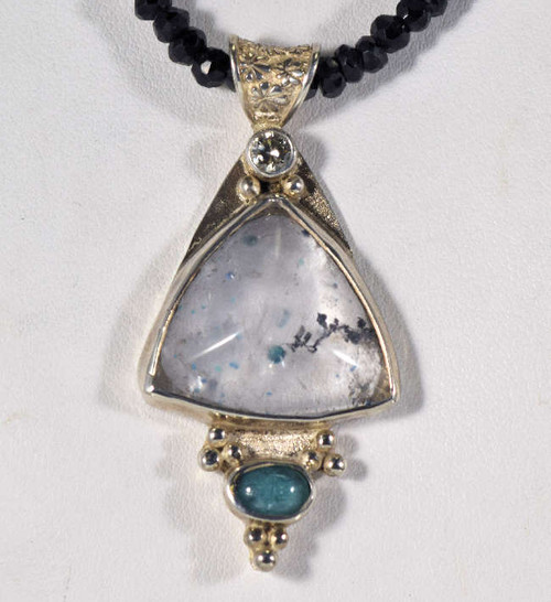 "The Paraiba tourmaline in quartz necklace is handcrafted in Portland, Maine. The piece is a real one of a kind. The triangle shaped quartz measures 22mm.x19mm.x18.5mm and also has black tourmaline in it. There is also an oval Paraiba cabochon on the bottom measuring 7mm.x5mm. At the top of the stone there is a round brilliant cut diamond that is .2carats. The color of the diamond is ""j"" and clarity is ""I1"". The stones are set in sterling silver and the pendant measures 2x1 inches and weighs 20.6grams. This is on a 4mm. faceted rondelle, black garnet strand. The necklace is 17.5 inches and length."
