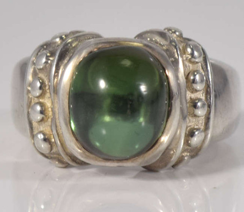 The oval green tourmaline byzantine ring is hand crafted in Portland, Maine.  The stone is a green tourmaline cabochon measuring 11 mm. x 10 mm. and is clear.  The stone is set in a sterling silver chunky beaded ring weighing 10.3 grams.  The ring is a size 6.